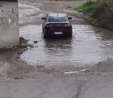حفرة مليئة بالمياه تعيق حركة السيارات وتشكل معاناة للمواطنين قرب جسر العقيبة في ريف جبلة (فيديو)